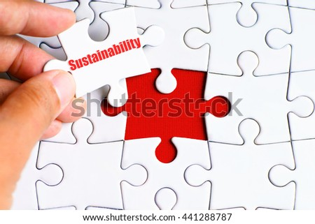 """A missing puzzle with a hand hold a piece of """"Sustainability"""" text puzzle want to complete it - business and finance concept - stock photo"""