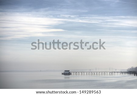 A misty day on the Chesapeake Bay with boathouse, Bay Bridge and lighthouse - stock photo