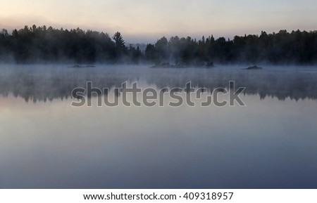 A misty morning on Sunbeam Lake in Algonquin Provincial Park, Ontario, Canada.  - stock photo