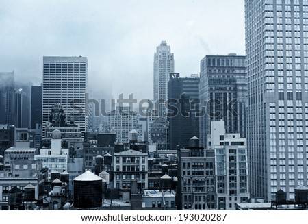 A misty New York City landscape with various architectural styles in blue tones. - stock photo