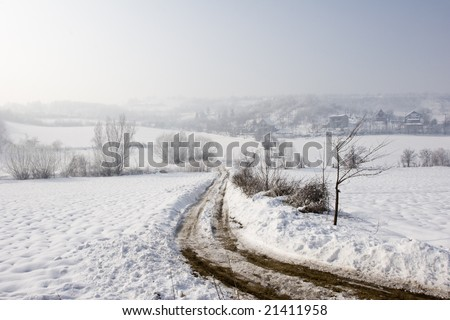 a misty winter view of farm track in the snow - stock photo