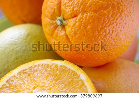 A mix of citrus fruits. Oranges and grapefruits on the plate. Fresh juicy citrus fruits. Colorful mix of exotic fruits. - stock photo