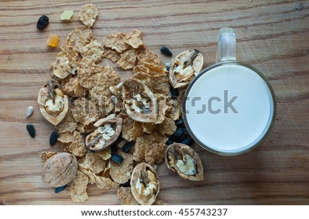 A mixture of grains, nuts, cereals and milk in a circle on a background tree. - stock photo