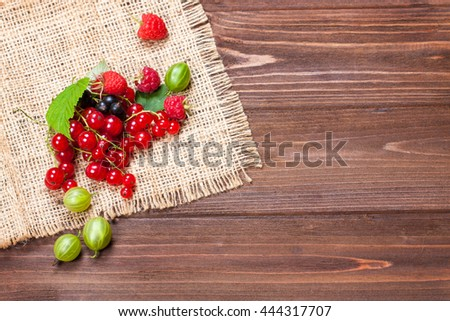 A mixture of ripe berries on a wooden table. Berries on a napkin, top view, empty space for text. Beautiful summer background - stock photo