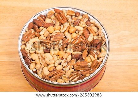 A mixture of salty, roasted deluxe nuts in a red plaid tin on wood table - stock photo