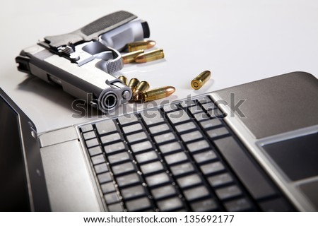 A 9mm handgun with scattered bullets beside it and part of a laptop computer. Back lit, shallow depth of field. - stock photo