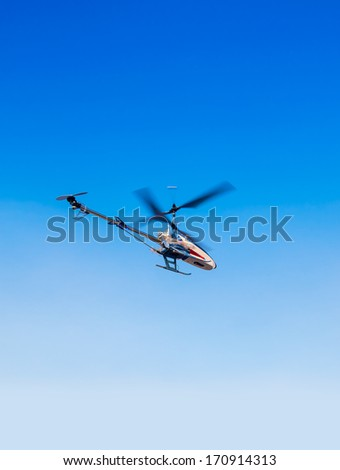 a model helicopter in flight, blue sky background - stock photo