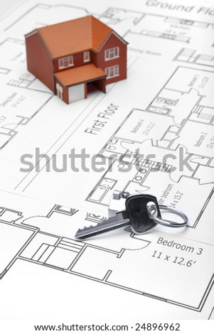 A model home and house key on architectural floor plans. - stock photo