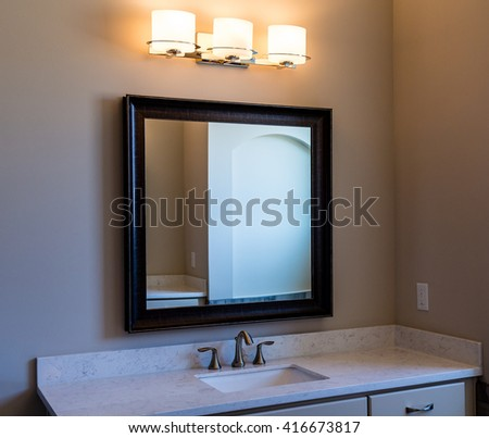 A Modern Bathroom with Vanity Mirror and Lights - stock photo