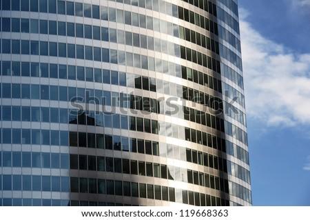 A modern building mirror facade illuminated by the sun - stock photo