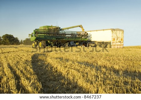 A modern combine harvester emptying grain into a truck - stock photo