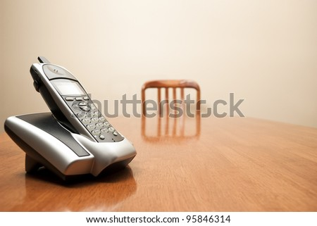 A modern cordless phone sits on an empty table - stock photo