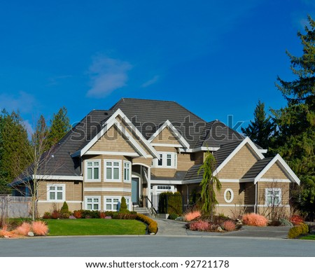 A modern custom built luxury house in a residential neighborhood. This high end home is very nicely landscaped property. - stock photo