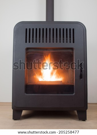a modern domestic pellet stove with a burning flame - stock photo