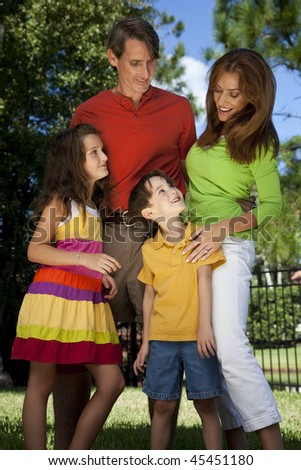 A modern family of father, mother, daughter and son playing together and having fun in a park - stock photo