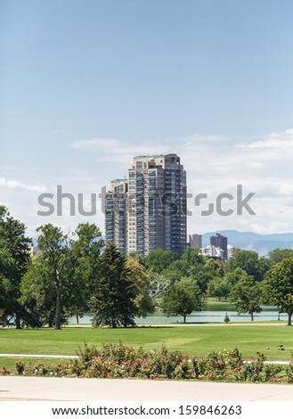 A modern high rise condominium building rising into sky beyond a green park - stock photo