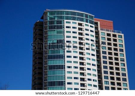 A modern high rise condominium tower rising into a clear blue sky - stock photo