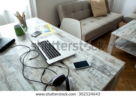 A modern home office setup on a wooden Table. - stock photo