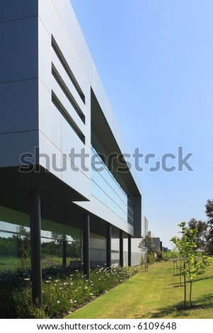 A modern industrial building, with surrounding garden beds, and clear blue sky. - stock photo