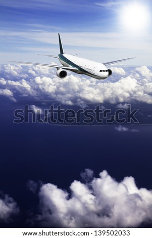 A modern jet airliner flies at high altitude over an island in the ocean. - stock photo