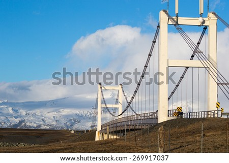 A modern suspension bridge connects the shore line disrupted by the glacier lagoon in Iceland. - stock photo