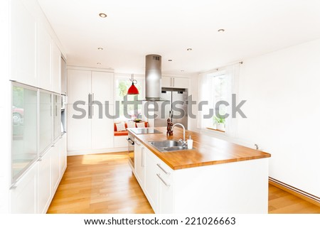 A modern Western kitchen interior of a fancy kitchen with kitchen island - stock photo