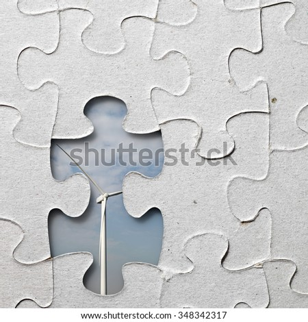 A modern wind turbine exposed through a jigsaw puzzle with a missing piece for the concept of solution to sustainable energy. - stock photo