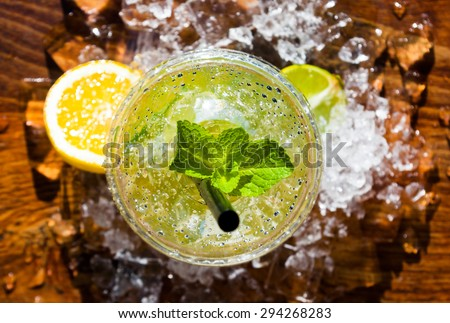 A mojito cocktail with mint leaf and a slice of lemon are lying onto layer of ice cubes in hot summer day. Summer alcoholic cocktails are great way to deal with the heat and high air temperature. - stock photo