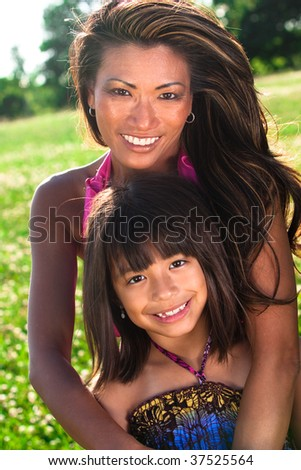 a mom and daughter hugging each other outside - stock photo