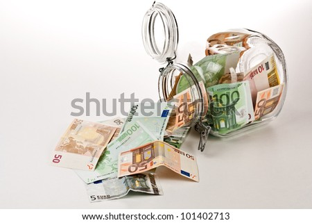 A Money jar full of savings, white background - stock photo