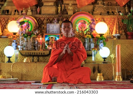 A monk praying in front of golden Buddhas, horizontal - stock photo