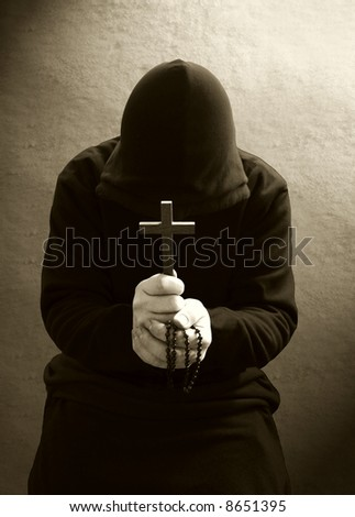 A monk praying with a rosary and crucifix in his hand. - stock photo