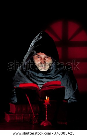 A Monk read mystical occult book in the dark - stock photo