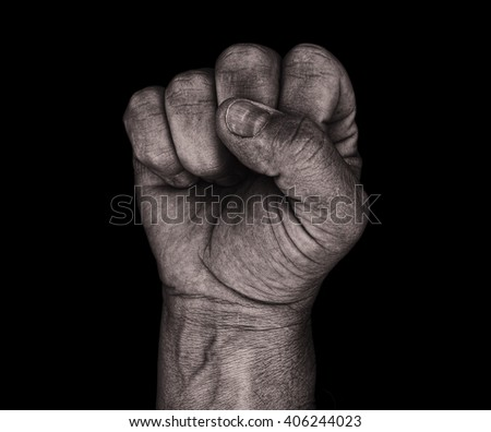 A monochrome adult male clenched fist isolated on a black background. - stock photo