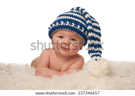 A 4 month old baby boy wearing a blue and cream colored, crocheted stocking cap. He has a slight grin and is looking at the camera. Shot in the studio on a white background. - stock photo