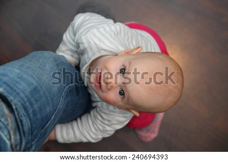 A 8 month old baby lifting up on the fathers leg - stock photo