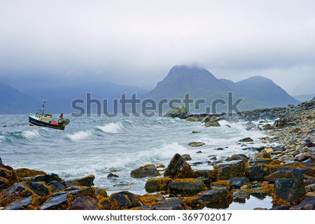 A moored boat on Loch Scavaig sitting out an incoming storm with low cloud and sea mist covering the distant Cuillin Hills in Summer, Elgol, The Isle of Skye, Scotland - stock photo