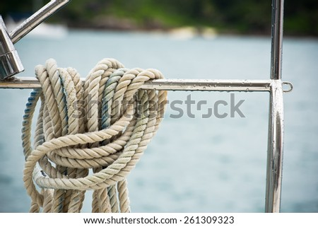 A mooring rope with a knotted end tied around a lifeline - stock photo