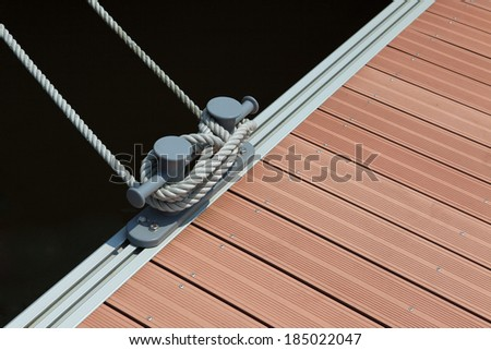 a mooring rope with a knotted end tightly tied around a cleat on a wooden pier/ Nautical mooring rope against dark blue sea water - stock photo