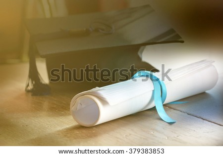 A mortarboard and graduation scroll tied with blue ribbon. - stock photo