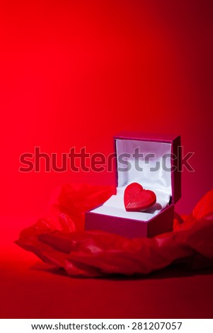 A most precious valentine themed still life image of a red love heart in a gift box.  Red background with copy space. - stock photo