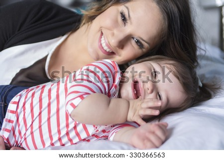 A Mother and baby playing and smiling on the bedroom - stock photo