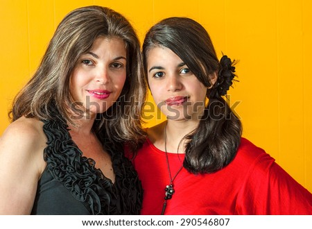 A mother and daughter in a close-up portrait that demonstrates family closeness. They are viewed in a head and shoulder pose looking at the camera with understated smiles.  - stock photo
