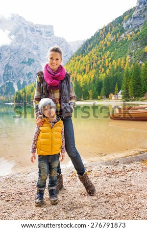 A mother and daughter standing on the shore of Lake Bries wearing outdoor gear. In the background autumn colours, green trees, and wooden boats are reflecting in the water. - stock photo