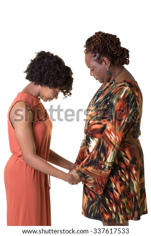 A mother and her daughter bowing their heads to pray, isolated - stock photo