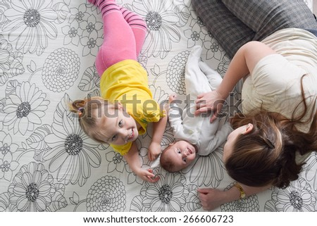 A mother and her four years old and three month old daughters lying playing on a bed. - stock photo