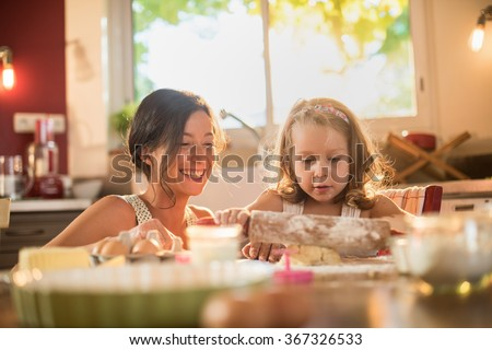 A mother and her four years old blonde daughter are cooking in a  kitchen. They are working on a pasty with a rolling pin on a wooden table full of ingredients and a green baking pan. Shot with flare - stock photo