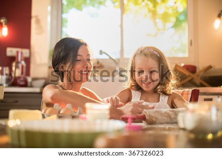 A mother and her four years old blonde daughter are cooking in a luminous kitchen. They are having fun, working on a pasty on a wooden table full of ingredients and a baking pan. Shot with flare - stock photo