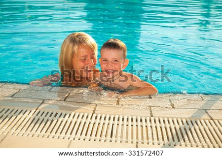 A mother and her son in the swimming pool - stock photo