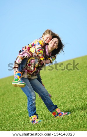 A mother and her young daughter playing in the meadow - stock photo